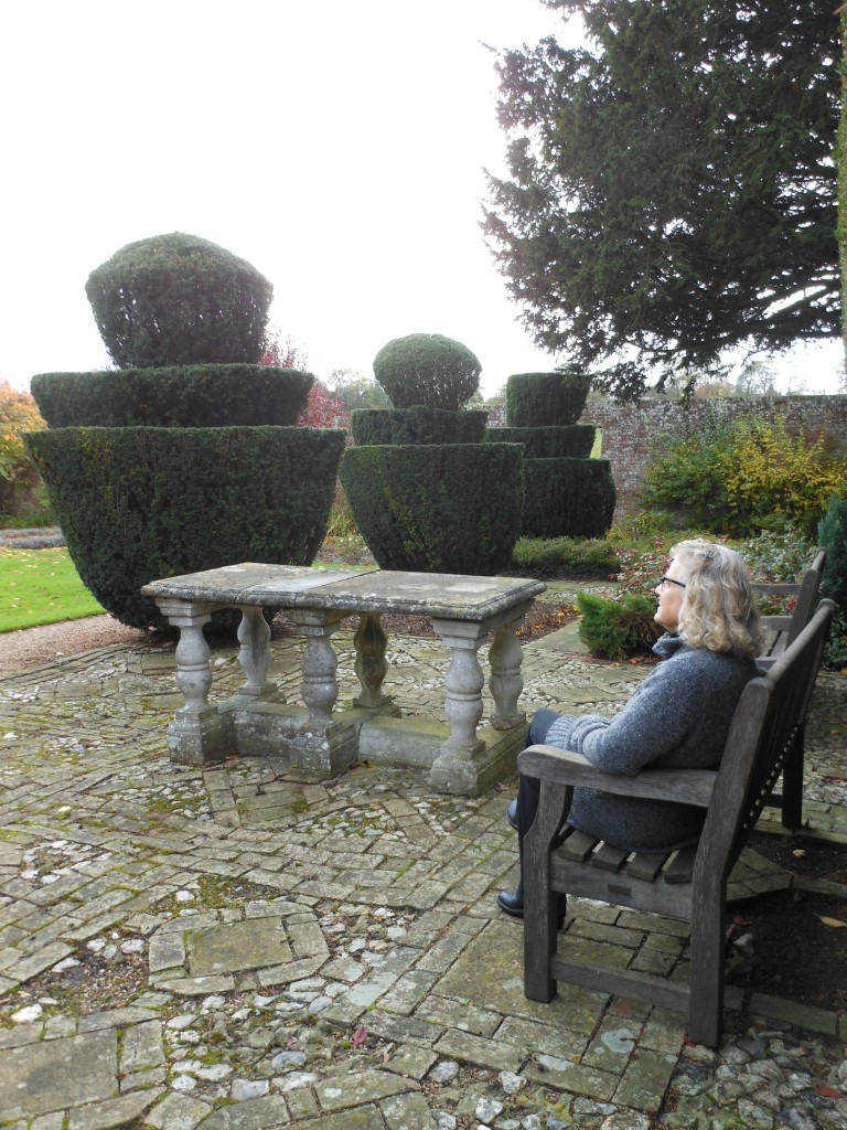 Autumn garden scene viewed by woman seated on bench
